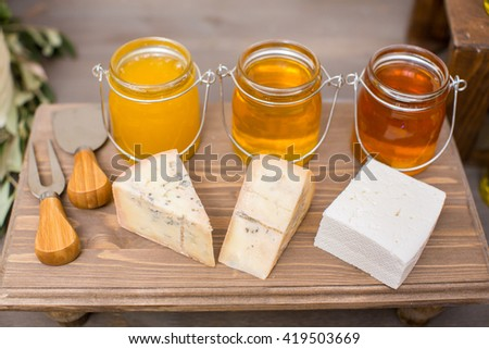 three kinds of cheese and honey on the wood board with olives - stock photo