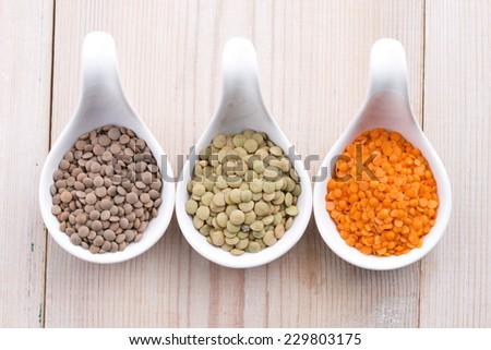 Three kinds of lentil in bowls - red lentil, green lentil and brown lentil  - stock photo