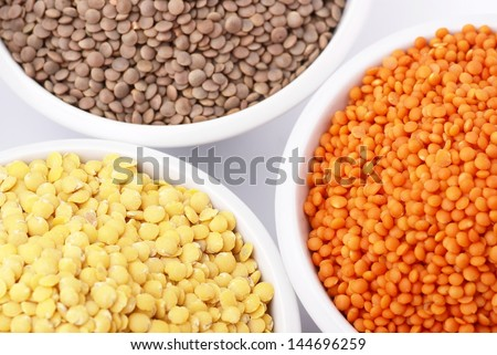 Three kinds of lentil in bowls - red lentil, yellow lentil and brown lentil - stock photo