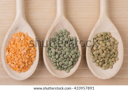 Three kinds of lentil on spoons - stock photo