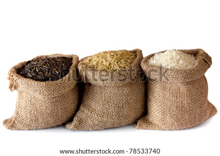 Three kinds of rice in small burlap bags isolated on white background - stock photo