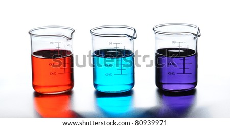 Three laboratory beakers with liquids of assorted colors. Closeup in horizontal format with reflections.