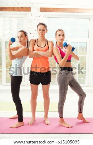 Three ladies with crossed and dumbbells