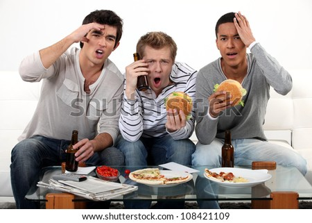 Three lads cringing at the television - stock photo