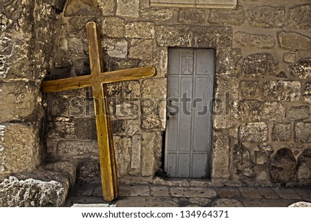 Three large scaled crucifixes resting on the wall of the Church of the Holy Sepulchre. These are used by pilgrims who carry them along the Via Dolorosa, reenacting the path Jesus Christ made. - stock photo