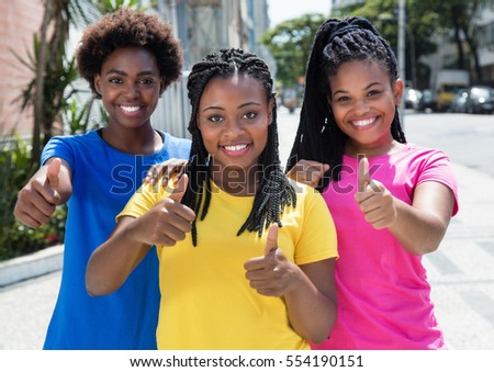 Three laughing african american woman showing thumb up