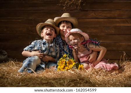 Three laughing children on hay in a hangar - stock photo