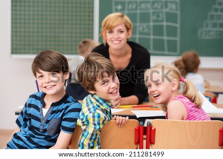 Three laughing happy school children turning in their chairs during class to laugh at the camera watched by a smiling young female teacher - stock photo