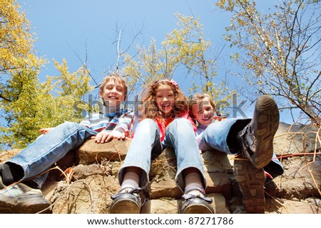 Three laughing kids sitting on the stone walls - stock photo