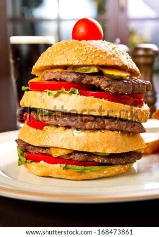 Three layered hamburger with fries - stock photo
