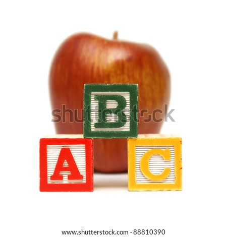 Three learning blocks are stacked up in front of a nice red apple for the young mind at work.