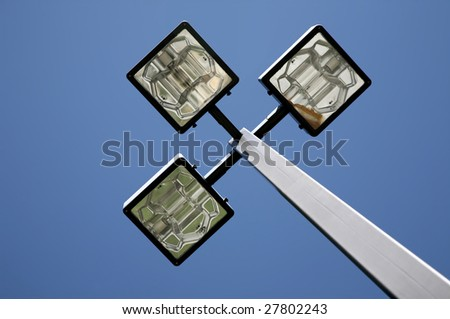 Three LED Street Lamps Affixed to an Iron Post Against a Deep Blue Sky - stock photo