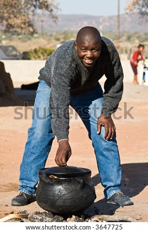 Three legged pot with traditional African food , setswa, African adult, people diversity series - stock photo