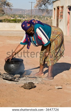 Three legged pot with traditional African food , setswa, African adult woman , people diversity series - stock photo