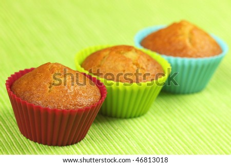Three lemon cupcakes in colorful silicone moulds on green background - stock photo