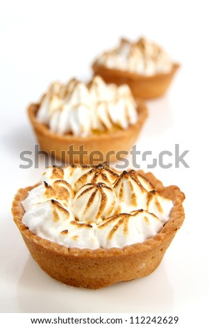 Three lemon pies in a row on a white background - stock photo