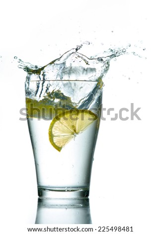 Three lemons are falling into the glass of water. - stock photo