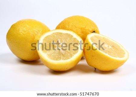 Three lemons, one cut in half, on white background