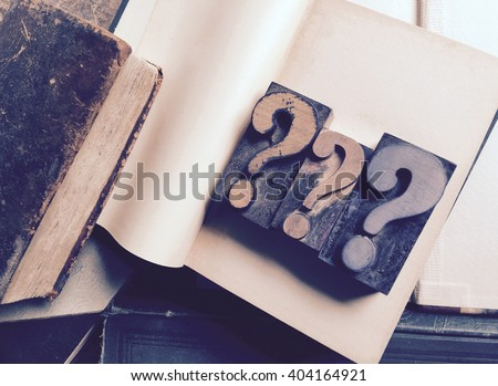 Three letterpress question marks on blank pages of vintage book - stock photo