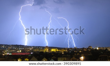 Three lightning strikes above cityscape. - stock photo