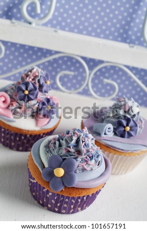Three lilac pink cupcakes on a dinner tray - stock photo