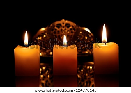 three lit candles on a black background