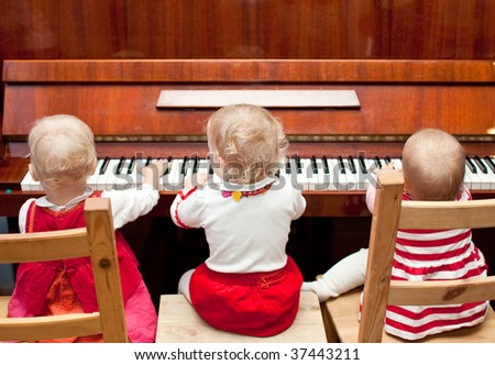 Three little baby girls playing a piano - stock photo