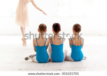 Three little ballerinas with personal ballet teacher in dance studio. classic ballet dancer  as teacher posing on a white background - stock photo