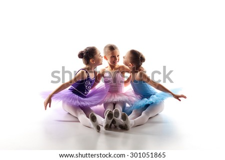 Three little ballet girls sitting  in multicolored tutu and pointe shoes together on white background - stock photo