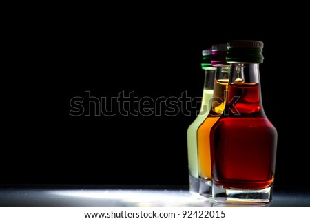 three little bottles against a black background,white shine on the ground - stock photo