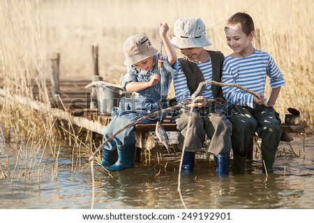 Three little boy is fishing at sunset on the lake - stock photo