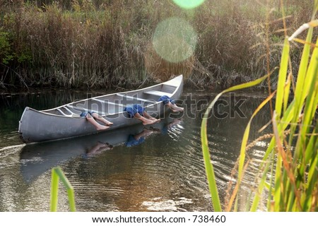 Three little boys napping in canoe on a  hot summer afternoon.  Sunspots intended. - stock photo