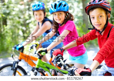 Three little children riding their bikes - stock photo