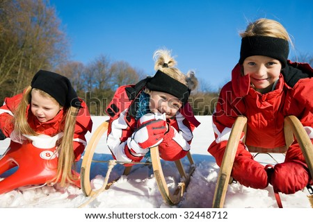 Three little children with their toboggan at the top of a hill in the snow waiting to start the fun - stock photo