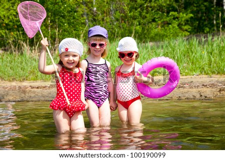 Three little cute girls go in water  together - stock photo