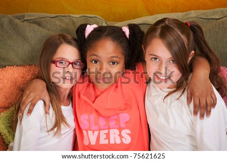 Three little friends hug each other on a couch - stock photo