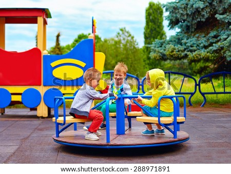three little friends, kids having fun on roundabout at playground - stock photo