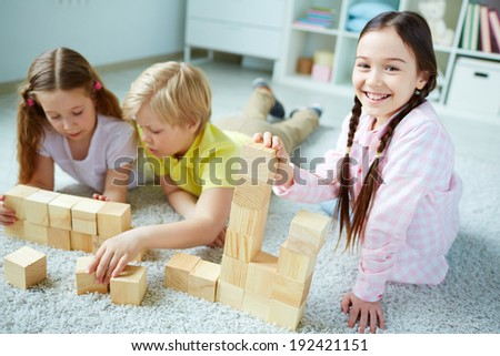 Three little friends playing with wooden bricks, happy girl looking at camera - stock photo