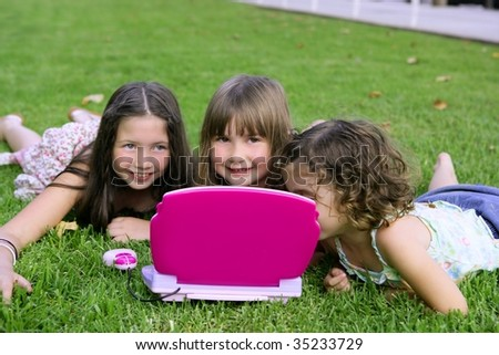 Three little girl outdoor playing with toy computer in grass - stock photo