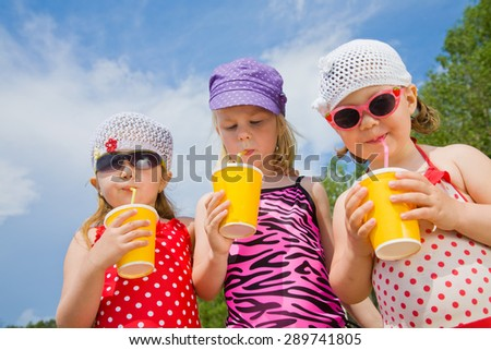 Three little girls drink cocktails at the beach through the ducts - stock photo