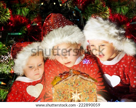 Three little girls in Santa hats looking on christmas house - stock photo