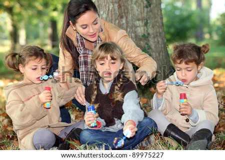 three little girls making bubbles in the forest - stock photo