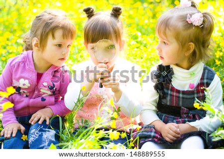three little girls  playing on green meadow with magnifying glass - stock photo