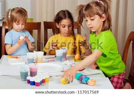 Three little girls (sisters) painting on Easter eggs at home kitchen - stock photo