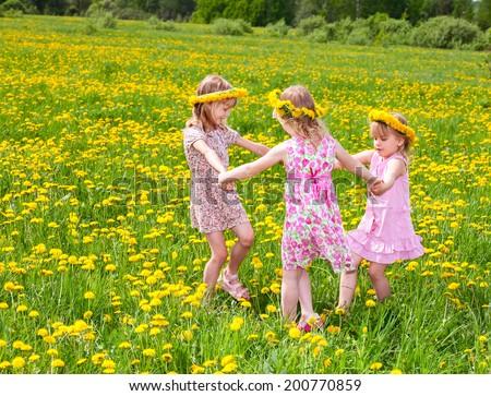 Three little girls wearing dandelion wreath enjoying a summer day outdoors - stock photo
