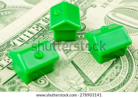 Three little green houses made of plastic are laying on one dollar banknote with the eye in the center - stock photo