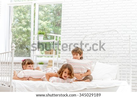 three little happy kids playing on white bed at home - stock photo