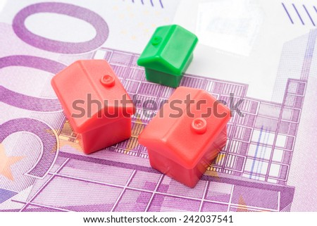 Three little houses made of plastic are laying on 500 euro banknote - stock photo