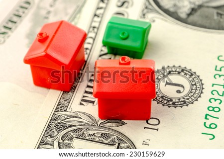 three little houses made of plastic are laying on one dollar banknote, business concept - stock photo