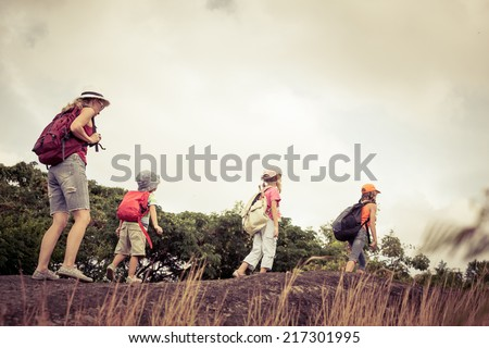 three little kids and mother in the mountains at the day time - stock photo